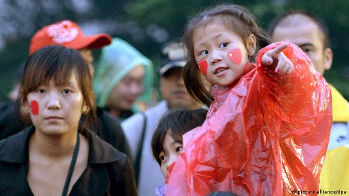 ©Kyodo/MAXPPP - 01/10/2013 ; BEIJING, China - A girl points at the Chinese flag being hoisted near Tiananmen Square in Beijing on Oct. 1, 2013, the National Day of China. (Kyodo)