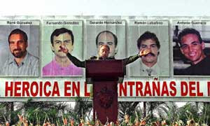 Fidel Castro gives a speach in front of photos of the five convicted Cuban spies