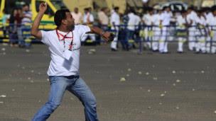Manifestante pró-Mubarak arremessa pedra contra ativista contrário ao ex-presidente diante da academia de polícia onde irá ocorrer o julgamento (Reuters)