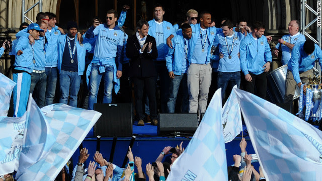 Manchester City manager Roberto Mancini applauds his players as they celebrate in front of their fans.