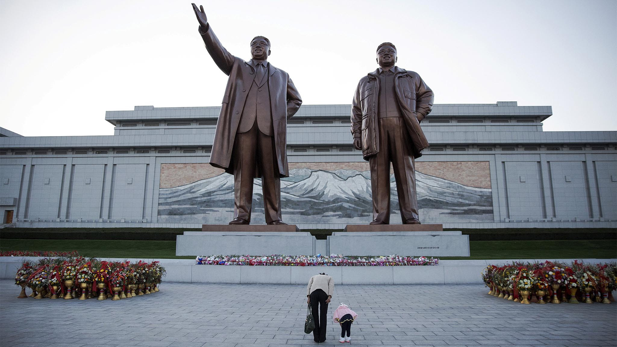 A woman and her daughter their respects at statues of North Korea founder Kim Il Sung (L) and late leader Kim Jong Il in Pyongyang