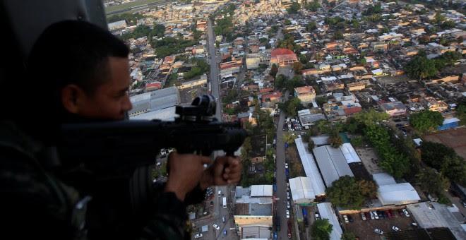 Un soldado hondureño con su fusil en un helicópero militar durante la operación denominada 'Paz y Democracia II', dentro de las medidas de seguridad en la campaña de las elecciones presidenciales. REUTERS/Jorge Cabrera