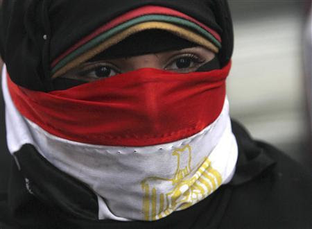 A woman, with the national flag covering part of her face, takes part in a protest rally against then Egyptian President Mohamed Mursi and members of the Muslim Brotherhood in front of the courthouse and the Attorney General's office, near Tahrir Square in Cairo, in this March 8, 2013 file picture. REUTERS-Amr Abdallah Dalsh-Files