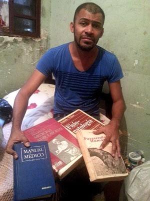 Cícero Pereira Batista, de 33 anos, mostra livros achados no lixo e com os quais estudou para virar médico (Foto: Raquel Morais/G1)
