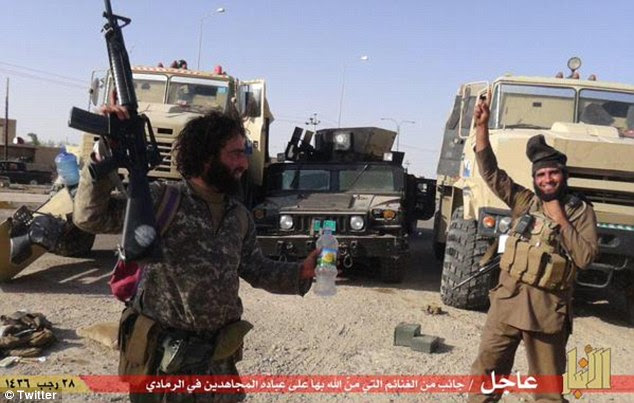 Spoils of war: Other pictures posted online purportedly show Islamic State militants celebrating after capturing military vehicles abandoned by fleeing Iraqi security forces