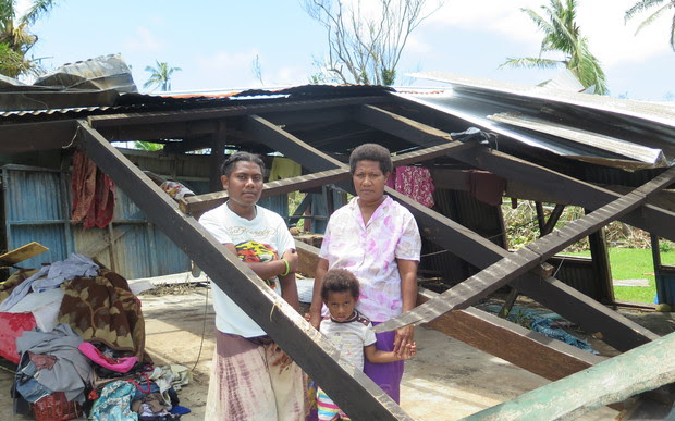 Usenia Nemai and daughters Rusila, 18, and Marie Grace, 5, stand at what used to be the lounge of their two-bedroom home in Driti village.
