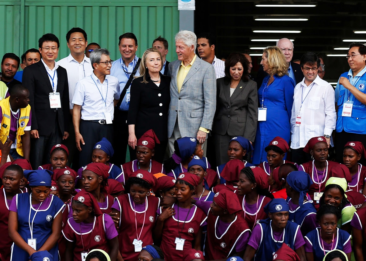 Former US president Bill Clinton and his wife, US Secretary of State Hillary Clinton, pose with workers at the grand opening cermony of the new Caracol Industrial Park in Caracol, Haiti, on October 22, 2012.