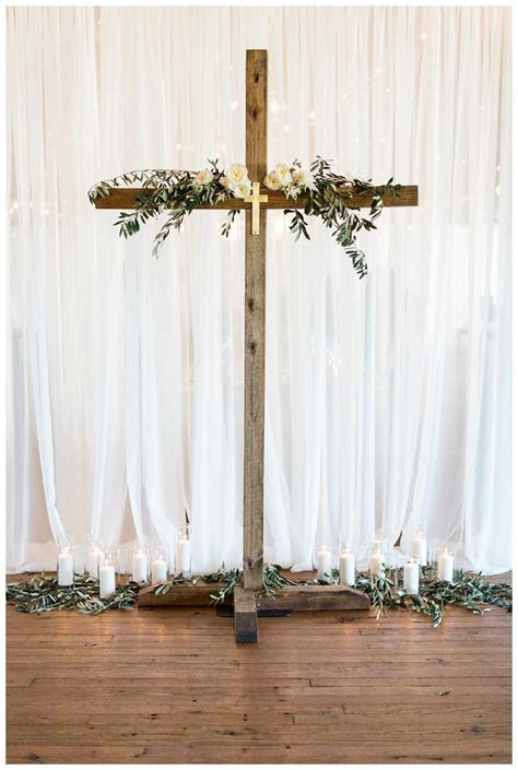 Wedding ceremony decor with a wooden cross, olive branches