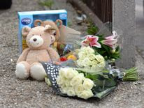 Toys and floral tributes have been left outside the house