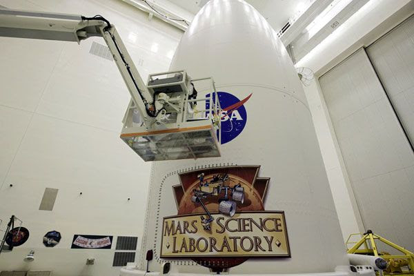 A worker applies a NASA 'Meatball' logo to the side of the Atlas V's payload fairing, on October 31, 2011.