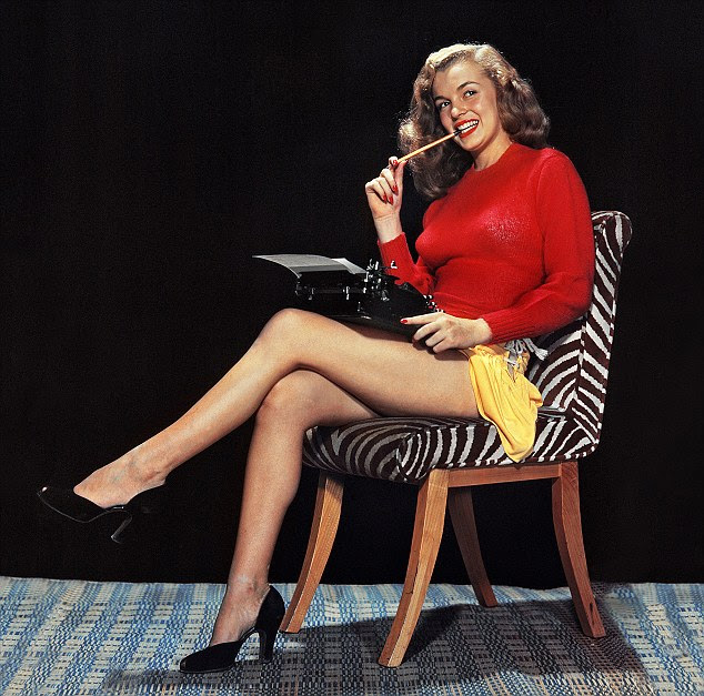 Typing cool: Marilyn strikes a pose in 1946. It was her 'magic red sweater' that helped catapult her into the limelight