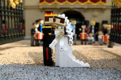 Lego models of Prince William and Kate Middleton share a kiss in front of a model of Buckingham Palace