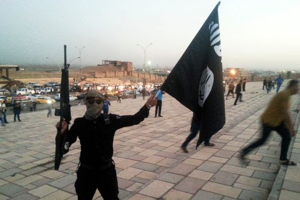 A fighter of the Islamic State of Iraq and the Levant (ISIL) holds an ISIL flag and a weapon on a street in the city of Mosul, June 23, 2014