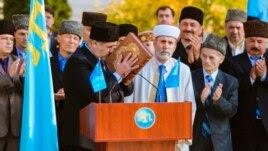 Глава Меджлиса Рефат Чубаров в ходе церемонии вступления в должность целует Коран, 1 ноября 2013 года
