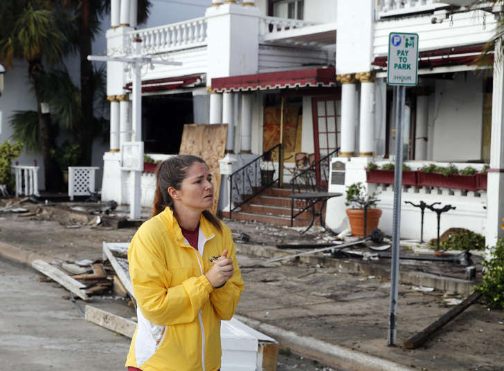 Sammantha Weber looks over storm damage from Hurricane Matthew at the Casablanco Inn Saturday, Oct. 8, 2016, in St. Augustine , Fla. Matthew plowed north along the Atlantic coast, flooding towns and gouging out roads in its path.