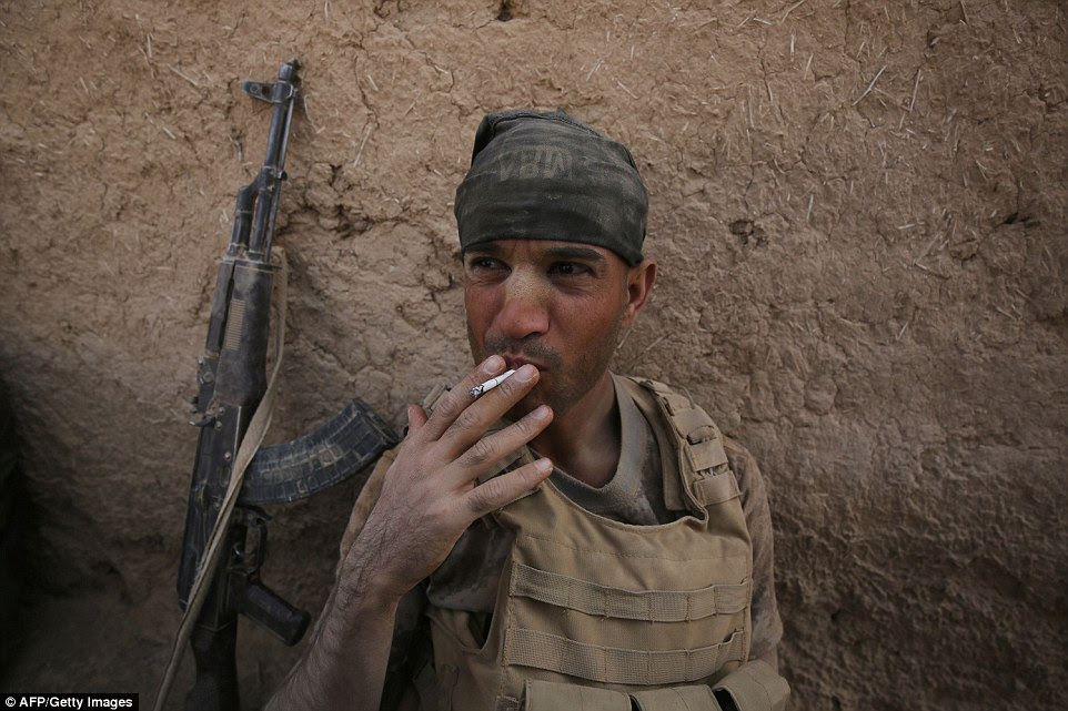 A member of the Iraqi government forces smokes a cigarette as they rest in the village of al-Khuwayn, south of Mosul, after recapturing it from ISIS