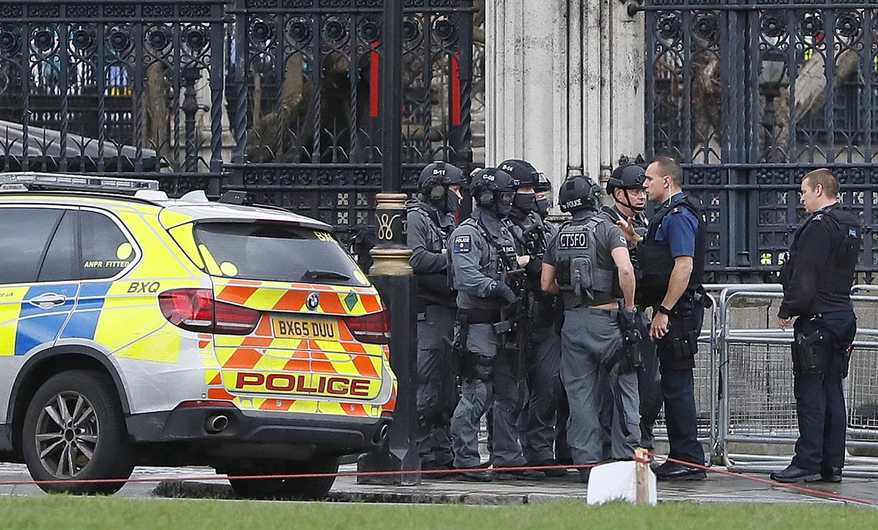 "Armed police officers gather outside of the Houses of Parliament in London, Wednesday, March 23, 2017 after the House of Commons sitting was suspended as witnesses reported sounds like gunfire outside. The leader of Britain's House of Commons says a man has been shot by police at Parliament. David Liddington also said there were ""reports of further violent incidents in the vicinity."""