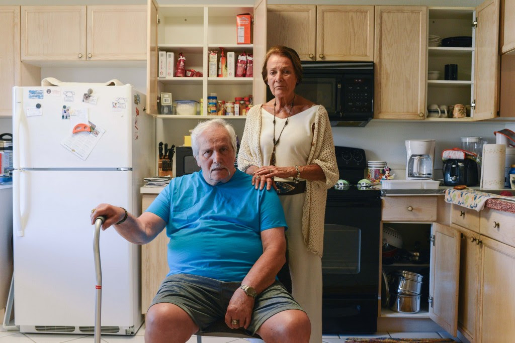Angelo and Mina Maffucci pose for a portrait in the kitchen of their son's apartment where they've been living for about five years since they've lost their house. Photo by Ariel Min/PBS NewsHour