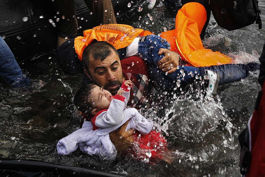 A Syrian refugee holds onto his children as he struggles to walk off a dinghy on the Greek island of Lesbos, after crossing a part of the Aegean Sea from Turkey to Lesbos (Yannis Behrakis, Thomson Reuters - September 24, 2015).
