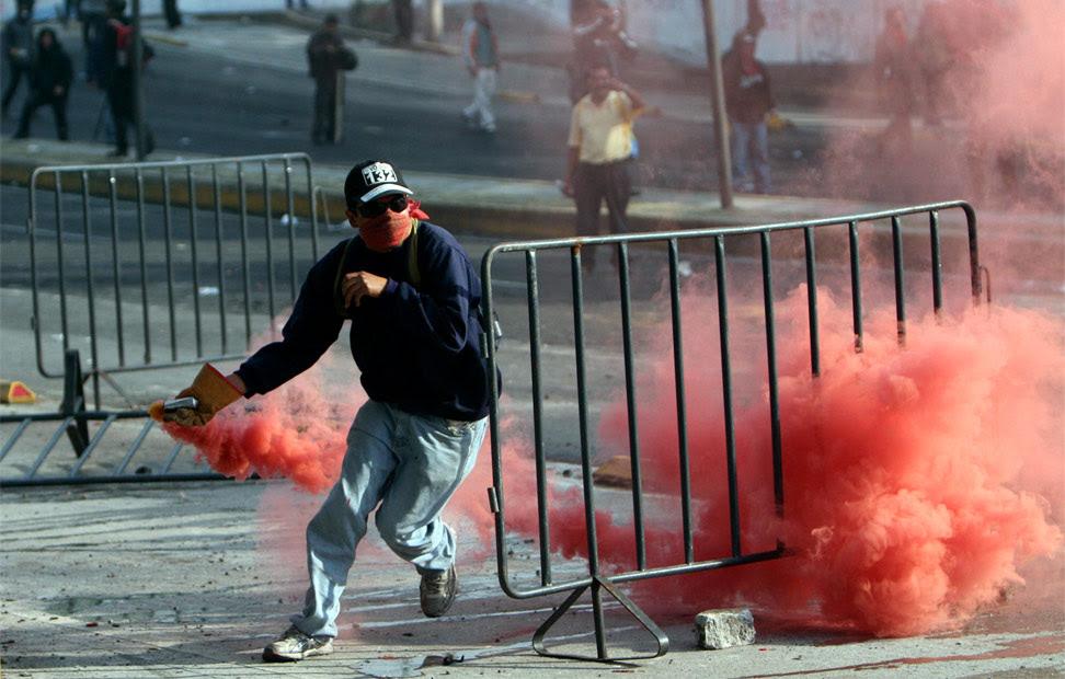 Un manifestante lanza una bomba de humo.