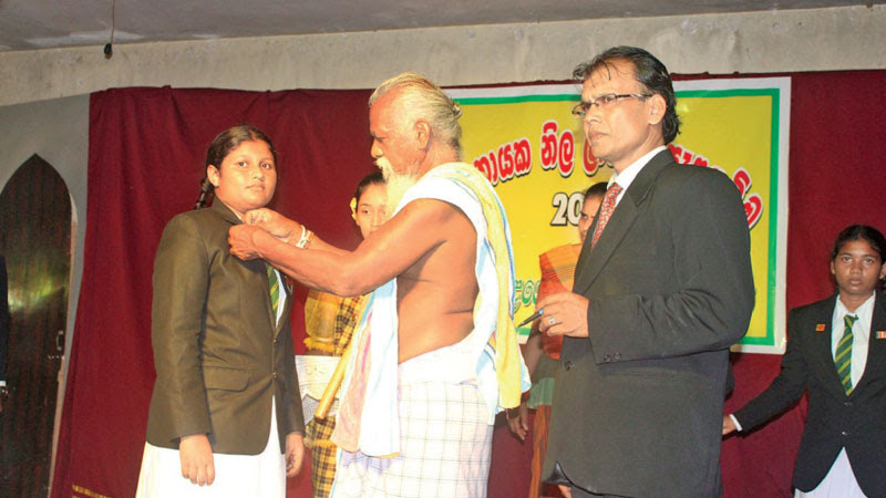 Uruwarige Wannila Aththo pinning a badge on a prefect. Picture by Sabaragamuwa Group Corr.