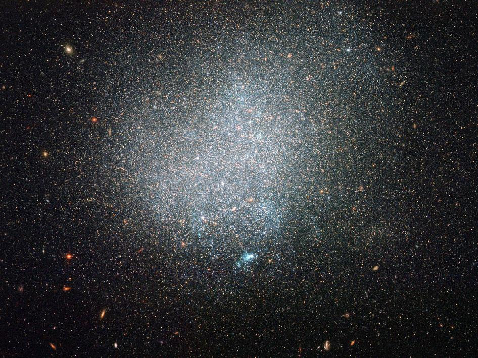 DDO 190 is classified as a dwarf irregular galaxy as it is relatively small and lacks clear structure. Older, reddish stars mostly populate DDO 190's outskirts, while some younger, bluish stars gleam in DDO 190's more crowded interior. Some pockets of ionized gas heated up by stars appear here and t