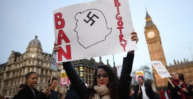 Una manifestante sujeta una pancarta en contra de las políticas antiinmigración de Trump. - AFP
