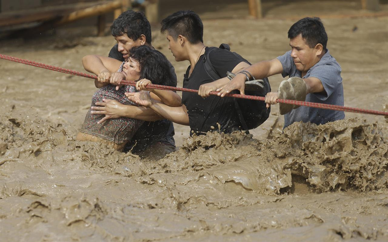 A group of people, stranded in flood waters, hold onto a rope as they walk to safety in Lima, Peru, Friday, March 17, 2017. Intense rains and mudslides over the past three days have wrought havoc around the Andean nation and caught residents in Lima, a desert city of 10 million where it almost never rains, by surprise.