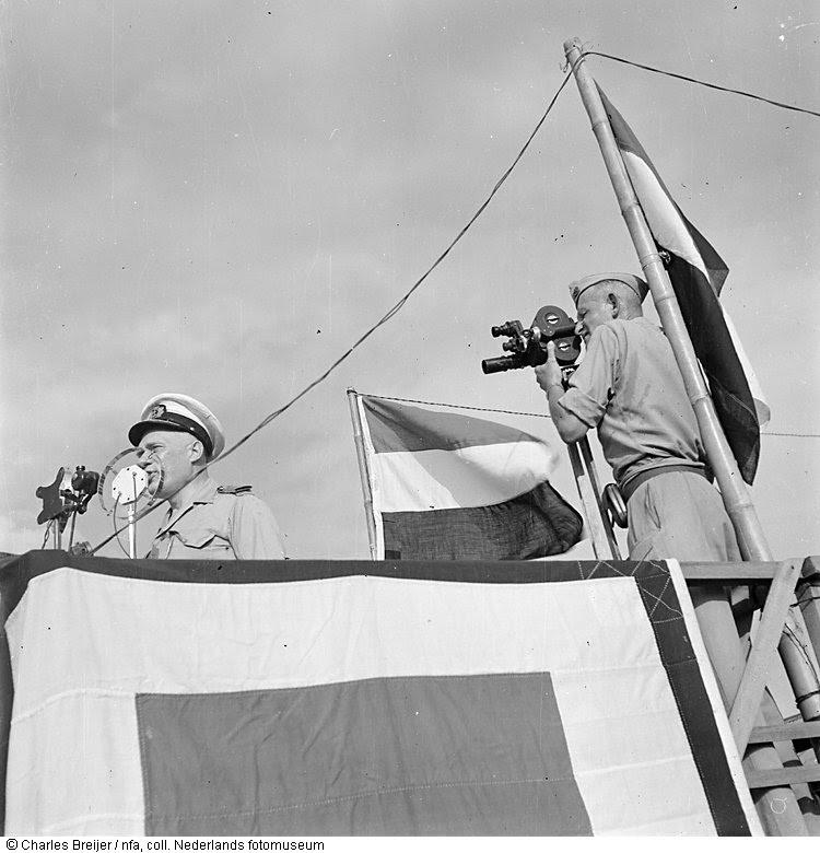 Jaap Zindler filmt vice-admiraal Pinke, terwijl hij een toespraak houdt vanaf een podium, Indonesië (z.j.)