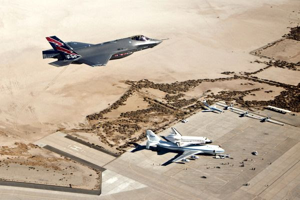 An F-35A Lightning II flies above space shuttle Endeavour and her Shuttle Carrier Aircraft just as they were about to depart from Edwards Air Force Base in the Mojave Desert and head for Los Angeles...on September 21, 2012.