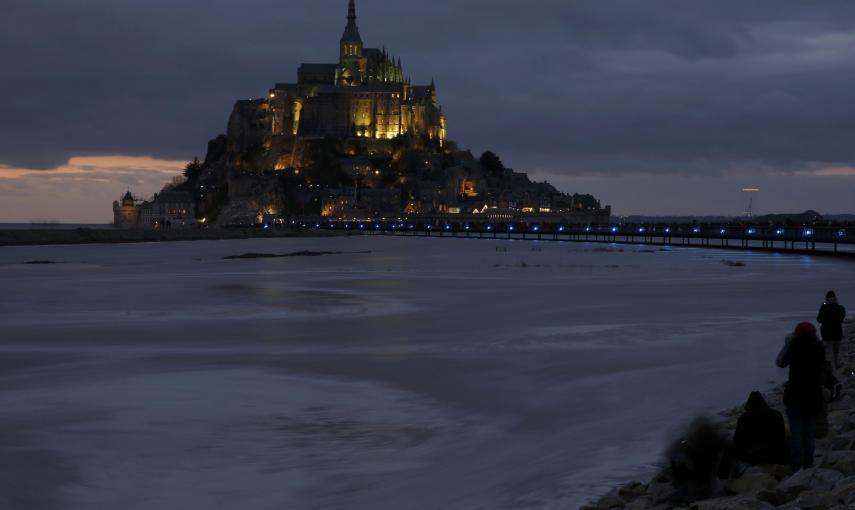 La gente se sienta en un terraplén para observar como la marea  rodea la abadía de Mont Saint-Michel, del siglo XI,en Normandía. REUTERS / Pascal Rossignol