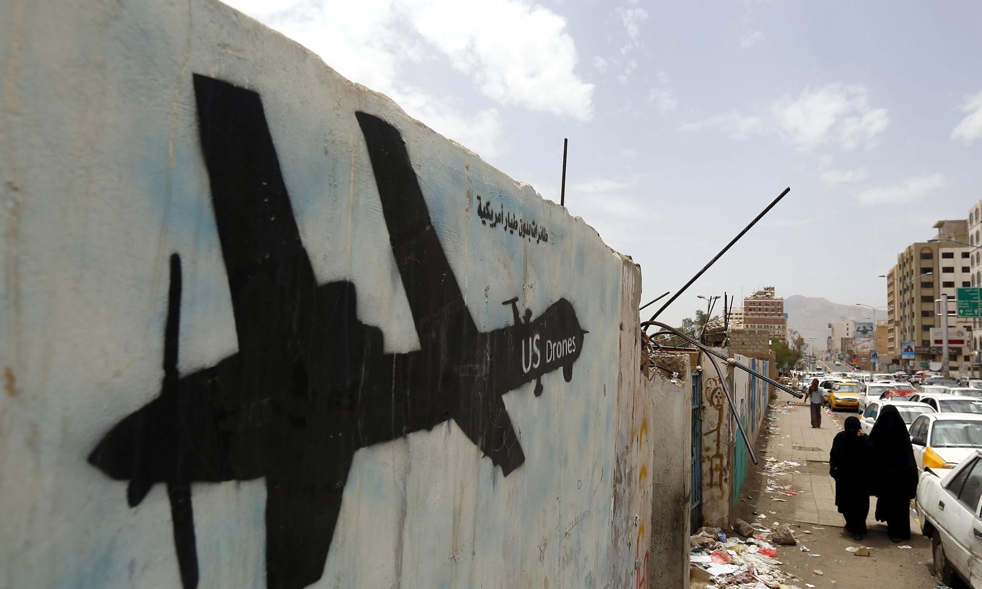 Yemenis walk past graffiti showing a US drone. Photograph: Yahya Arhab/EPA