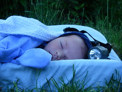 Baby Peter sleeping on his changing pad wearing a headlamp.