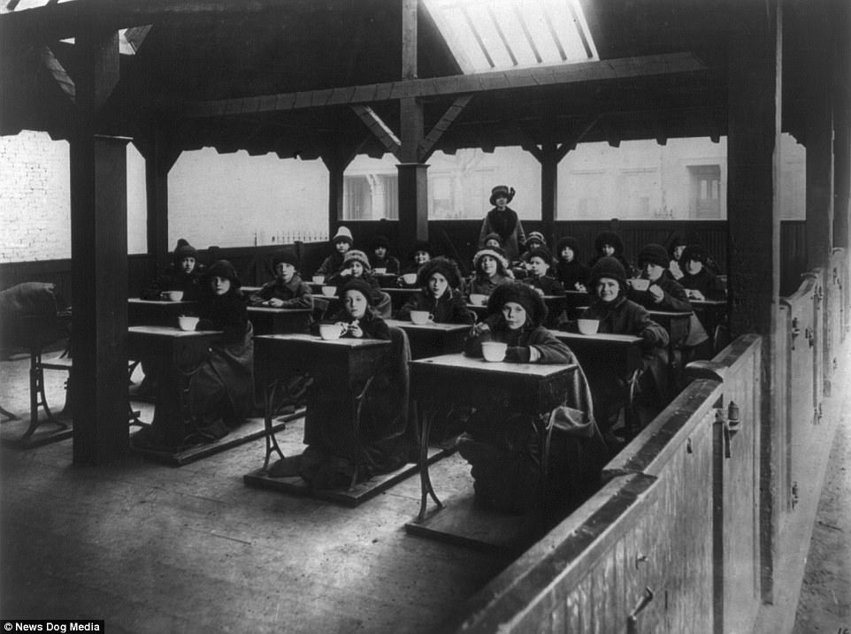 Children are pictured eating at their desks whilst dressed in winter clothing at an Open-air School in South Boston, circa 1910