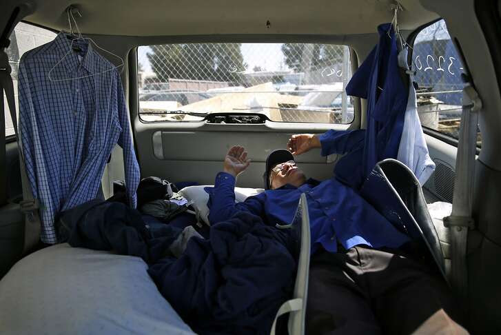 Apple bus driver Scott Peebles naps in his van between shifts in San Jose , Calif., on Thursday, Aug. 27, 2015.
