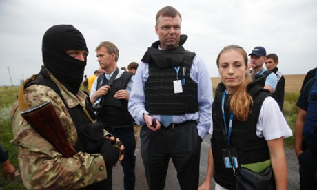 OSCE monitors speak with a pro-Russian separatist at the crash site of Malaysia Airlines flight MH17.ukraine