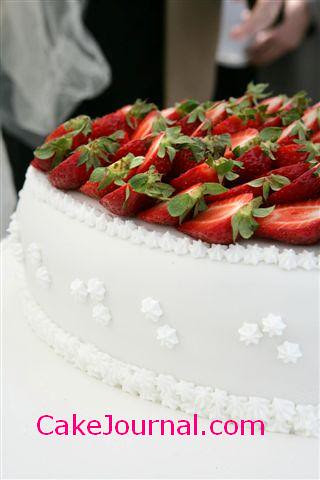 White wedding cake with fresh strawberries detail