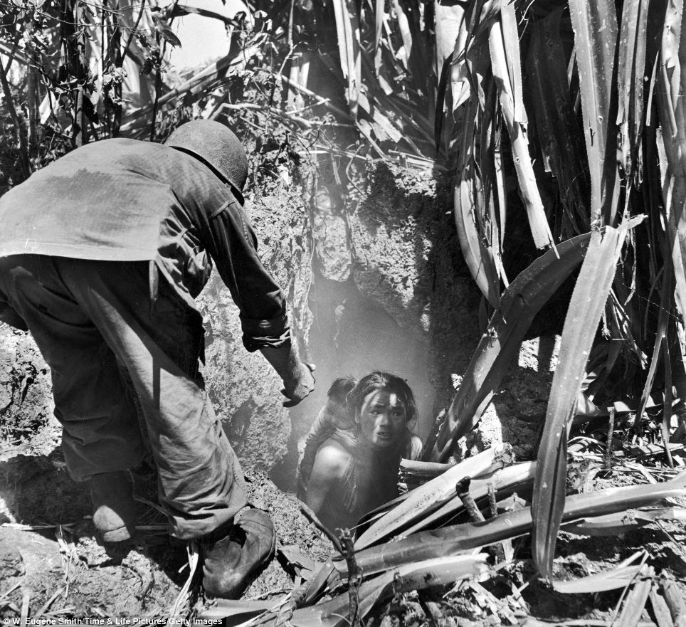 Helping hand: An American  soldier offers his hand to a woman emerging from a cave where she had hidden with her child during the battle between Japanese and American forces for control of Saipan, Northern Mariana Islands in July 1944