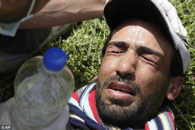 A man washes his face with water after he was struck by the tear gas on the border of Macedonia and Greece