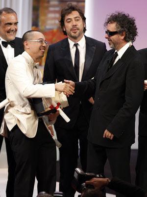 O diretor Apichatpong Weerasethakul, ao lado do ator Javier  Bardem, recebe a Palma de Ouro de Tim Burton
