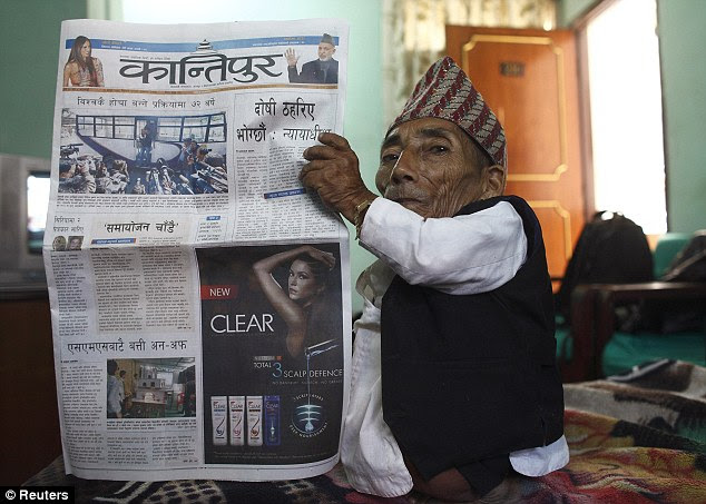 Chandra Bahadur Dangi, 72, poses with a local newspaper to show his tiny frame