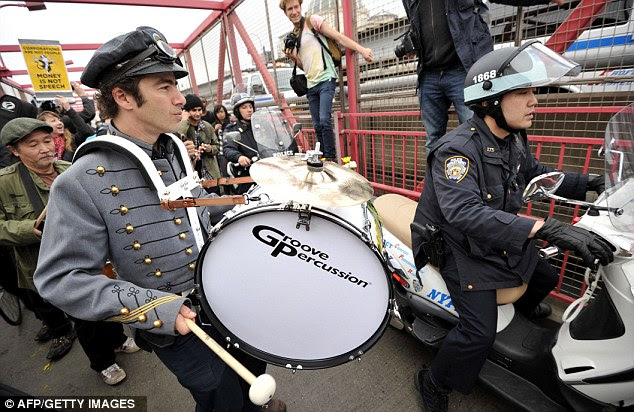 Force: An officer tries to squeeze through the crowd - which included a full marching band - on the bridge