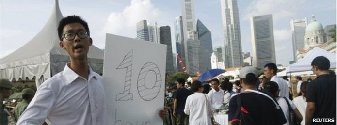 Man with a sign saying queue length is ten hours in Singapore (27 March 2015)
