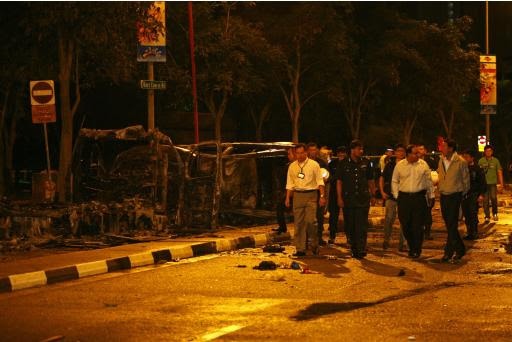 Singapore's Deputy PM Teo and Minister in Prime Minister's Office Iswaran look at the site of two burnt vehicles following a riot in Singapore's Little India district