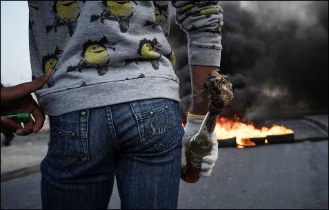 Un manifestante sostiene un 'cóctel molotov' durante los enfrentamientos con las fuerzas de seguridad de Bahrein. Protestan por la muerte de Habib Ebrahim, quien habría muerto por inhalar gases lacrimógenos que la policía utilizó para disolver una marcha en octubre de 2012.