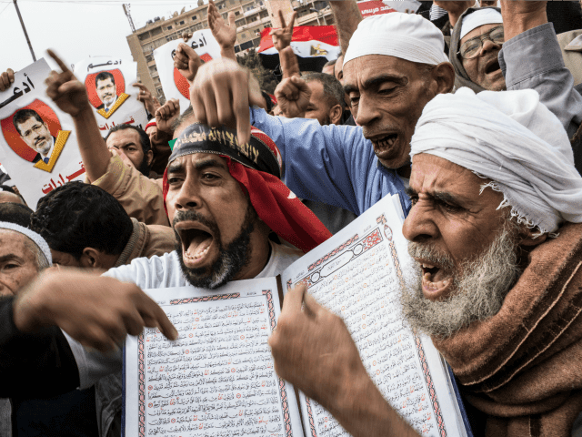 Supporters of Egyptian President Mohamed Morsi and members of the Muslim Brotherhood chant slogans during a rally on December 14, 2012 in Cairo, Egypt. Opponents and supporters of Egyptian President Mohamed Morsi staged final rallies in Cairo ahead of tomorrow's referendum vote on the country's draft constitution that was rushed through parliament in an overnight session on November 29. The country's new draft constitution, passed by a constitutional assembly dominated by Islamists, will go to a referendum vote on December 15. (Photo by Daniel Berehulak/Getty Images)