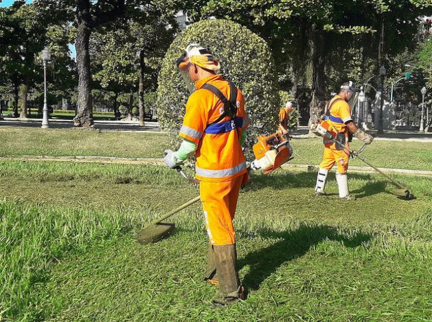 Young municipal workers wear uniforms and other protective equipment while cutting the grass in the Praça Paris park in the Gloria neighbourhood in Rio de Janeiro, Brazil. The lack of training and the breach of safety requirements by their employers make young Latin Americans the most vulnerable to accidents at work. Credit: Fabiana Frayssinet/IPS