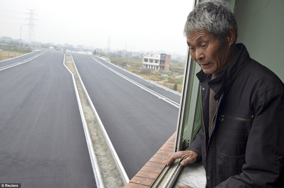 Luo Baogen looks out on the new road to the city's railway station which is yet to be officially opened