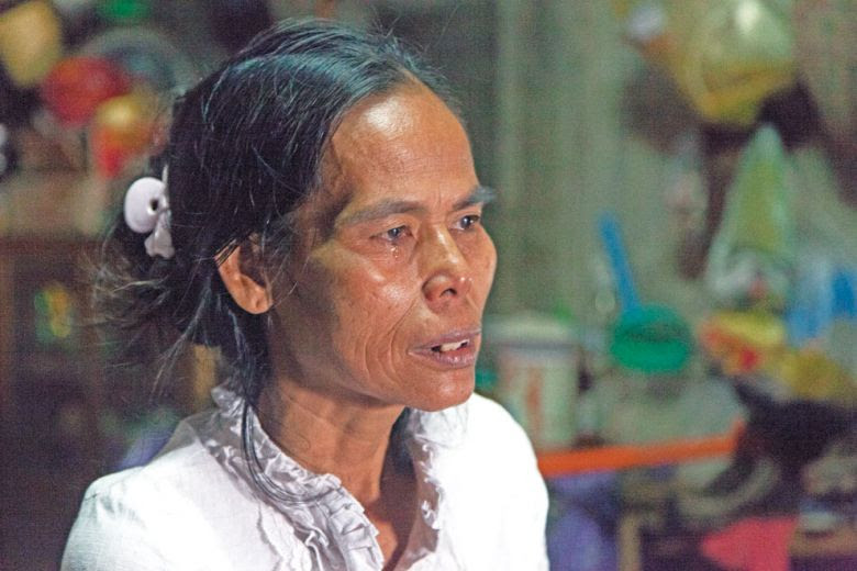 Tith Narin, the wife of CNRP activist Ouk Pich Samnang, sits at her house in Phnom Penh yesterday and cries after losing her son to cancer and having her husband imprisoned on Tuesday.