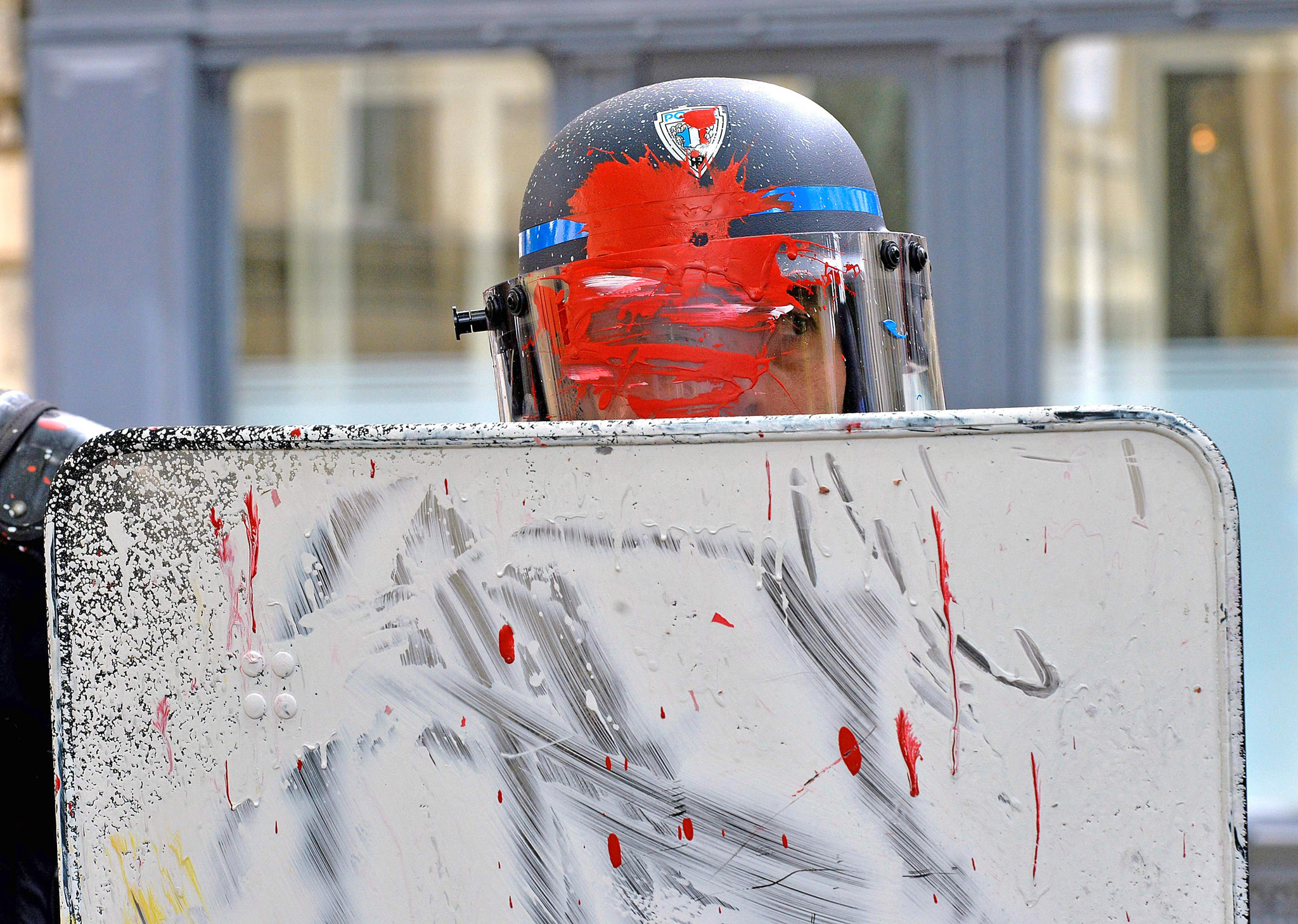 "TOPSHOT - French riot police officers stand guard after receiving some paint on their uniform, during a demonstration to protest against the government's labour reform on May 19, 2016 in Bordeaux.  France was disrupted by a third straight day of strikes and demonstrations on May 19 as the prime minister called for protesters who torched a police car to face ""harsh"" punishment. The labour reforms have sparked two months of protests on France's streets, drawing 68,000 nationwide on Tuesday, police said, while organisers put the turnout at 220,000"